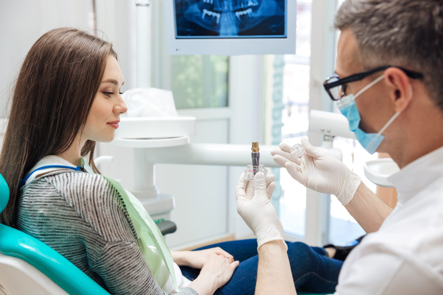 Male Dentist Showing His Female Patient A Dental Implant