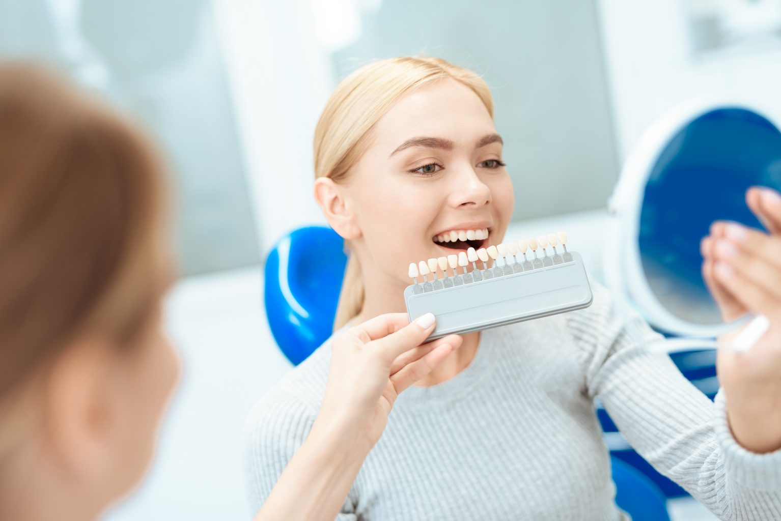 A Woman Came To See A Dentist For Teeth Whitening. The Dentist Determines The Color Of Her Teeth