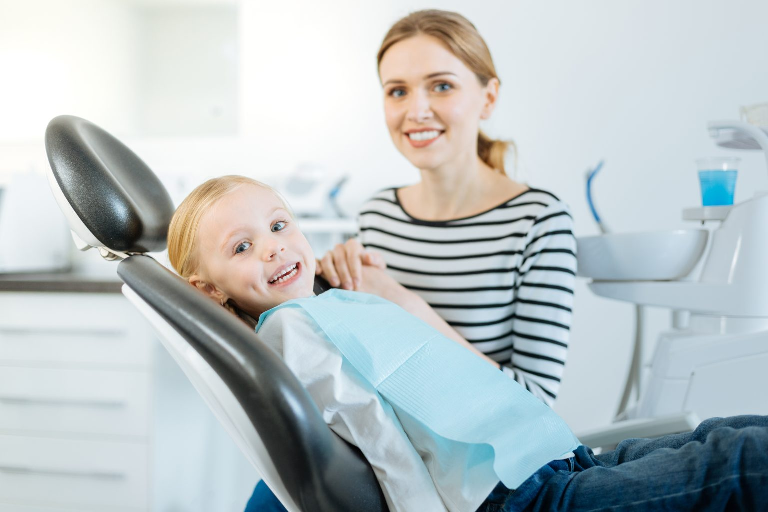 Cute Little Patient And Her Mother Posing In Dentist Office