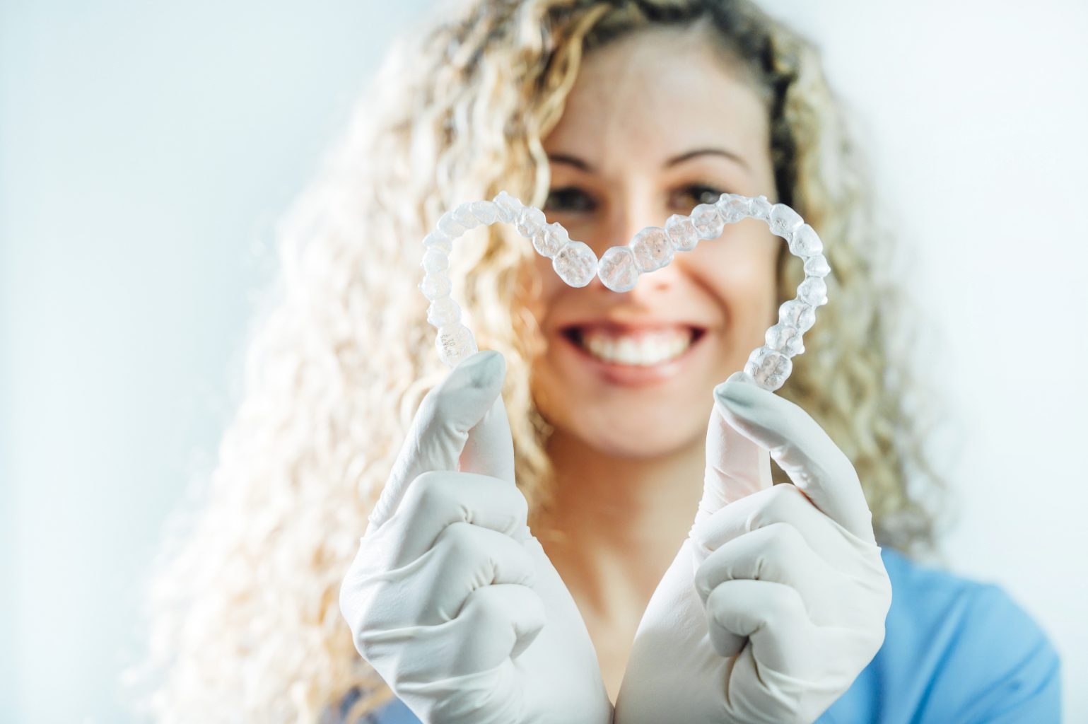 Female Doctor Holding Two Transparent Heart Shaped Dental Aligners